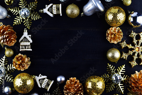 Christmas party decoration concept, gold and silver Christmas ornaments on black/dark wooden background, frame and space for text