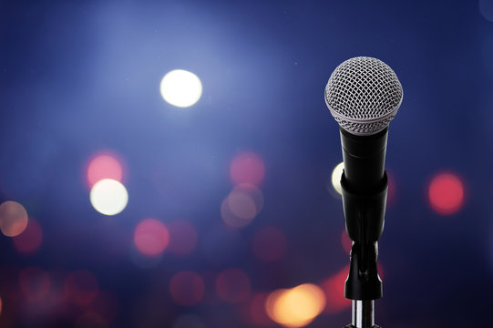 Microphone on stage ..Close up of microphone setting on stand with colorful light bokeh background in conference hall .