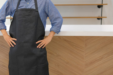 business owner wearing apron standing at cafe coffee shop restaurant counter bar - fototapety na wymiar