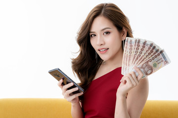 beautiful attractive elegance asian woman in red dress  sit and relax model pose hand hold money and smartphone on yellow sofa studio photo shoot
