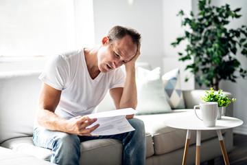 Bad news. Depressed mature man holding paper