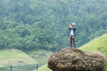 Hiking young Asian traveler man taking photo on the rock outdoors scenic mountain background. Lifestyle and relaxation concept.