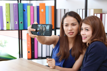 Smiling young Asian business women taking a picture or selfie together in office.