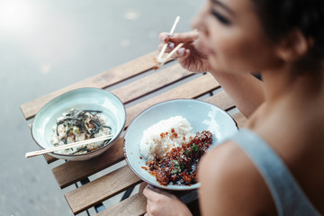 Beautiful woman eating chicken with rice in street cafe of chinese food.