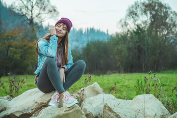 Portrait of young hipster girl enjoying an amazing view of mountains, pretty female traveler, sitting on large stones
