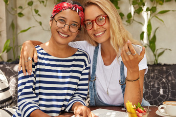 Friendly mixed race women with positive expression, embrace each other while spend free time in cafeteria, wear spectacles, have toothy smiles, hold mobile phone, being in good mood. Frienship concept