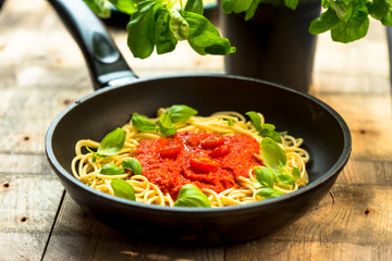 pasta with herbs, basil and tomato sauce served in a frying pan