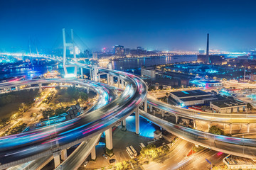 Scenic view on famous bridge in Shanghai, China at night. Multicolored nighttime skyline. Travel background.