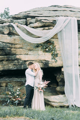 Wedding ceremony in the mountains in nature. Decor in the style of fine art. Summer stylized photo shoot