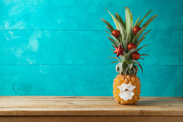 Christmas holiday concept with  pineapple as alternative Christmas tree  with ornaments on wooden table with copy space