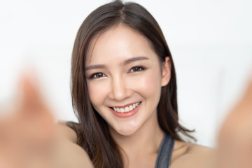 Close-up of young Asian beautiful woman  in sports clothing holding camera and smiling while taking selfie. Isolated white background.Beauty and Healthy Woman.