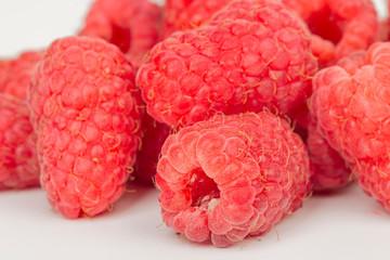 ripe juicy raspberries on white table