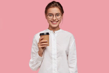 Horizontal shot of happy Caucasian girl in white shirt, carries paper cup with coffee, suggest you to have drink, wears round optical glasses, isolated over pink background. Pople, leisure and break