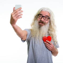 Studio shot of happy senior bearded man smiling and holding red