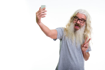 Studio shot of happy senior bearded man smiling and giving peace