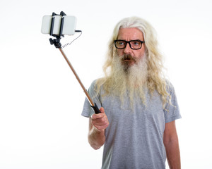 Studio shot of senior bearded man wearing eyeglasses and taking