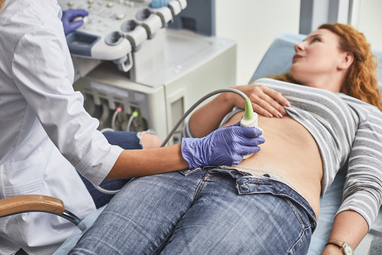 Expecting pregnancy. Doctor in white lab coat and sterile gloves examining red-haired woman with ultrasound scanner