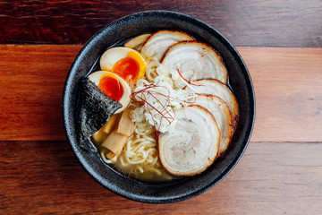 Miso Chashu Ramen: Japanese noodle in Miso soup with chashu pork, boiled egg, dry seaweed and chives in black bowl on wooden counter.