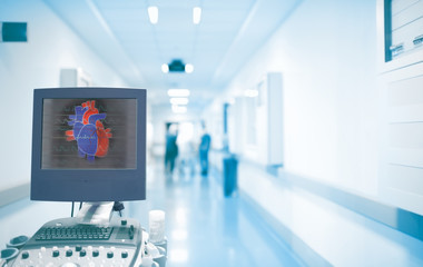 Ultrasonography equipment with heart image on the screen in the ER hallway with working doctors. Concept of an emergency care in a hospital with heart disease
