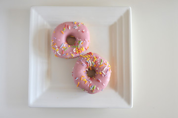 Two Sweet Pink Doughnuts Confection Served on a Square White Plate
