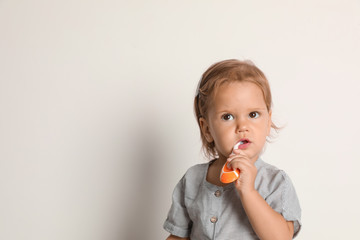 Cute little girl with toothbrush and space for text on white background