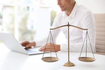 Scales of justice and blurred notary with laptop on background