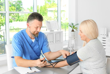 Male medical assistant measuring female patient blood pressure in clinic