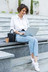 Young beautiful woman sitting outdoors using laptop computer.