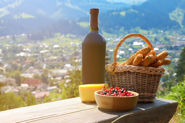 Bottle of red wine and food for picnic on bench against mountain landscape