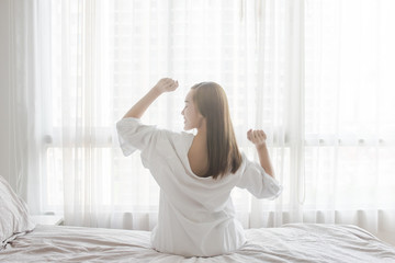 Beautiful Asian Woman stretching in bed after wake up, back view
