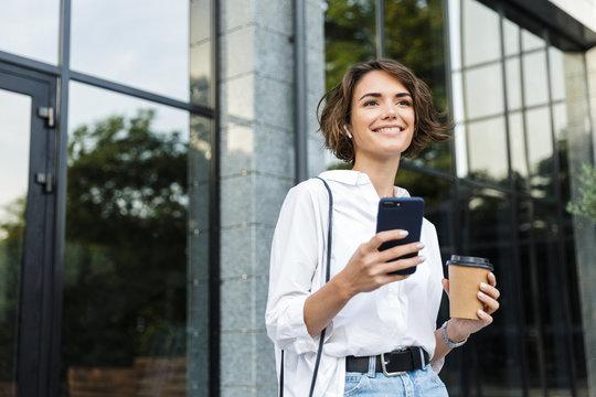 Beautiful young woman in earphones standing outdoors