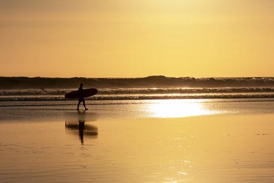 Silhouette of surfer and surfboard during sunset in Seminyak beach, Kuta, Bali, Indonesia.