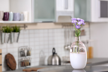 Vase with beautiful flowers on table in kitchen interior. Space for text