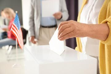 Elderly woman putting ballot paper into box at polling station, closeup