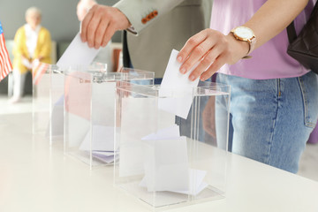 People putting ballot papers into boxes at polling station, closeup