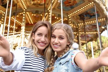 Attractive women taking selfie in amusement park