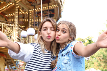 Attractive women taking selfie in amusement park