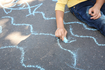 Little child drawing with colorful chalk on asphalt, closeup