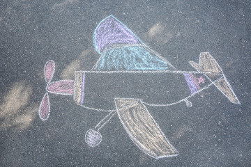 Child's chalk drawing of airplane on asphalt, top view
