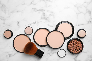 Flat lay composition with various makeup face powders on marble background. Space for text