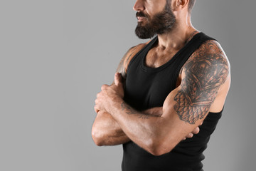 Tattooed man on grey background, closeup view. Space for text