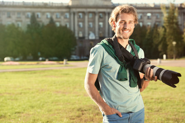 Handsome male photographer holding professional camera on street. Space for text