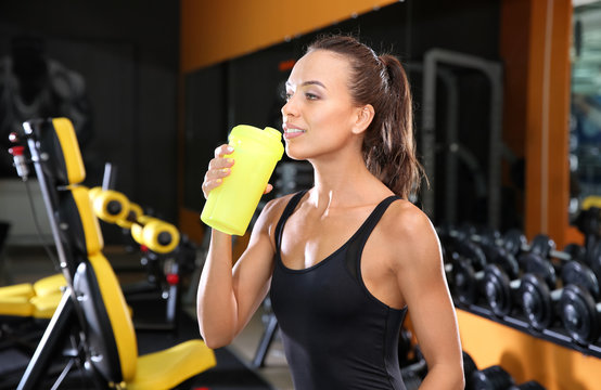 Portrait of athletic woman with protein shake in gym