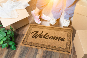 Man and Woman Standing Near Welcome Mat, Moving Boxes and Plant