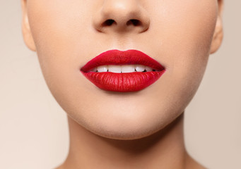 Beautiful young woman with red lips on color background, closeup