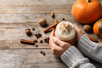 Woman holding glass of tasty pumpkin spice latte on wooden table, closeup with space for text