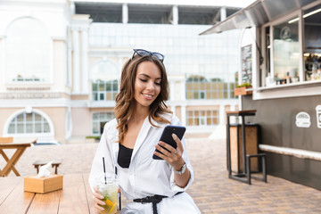 Smiling young woman sitting at the cafe outdoors