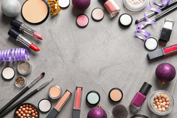 Flat lay composition with makeup products and Christmas decor on gray background. Space for text
