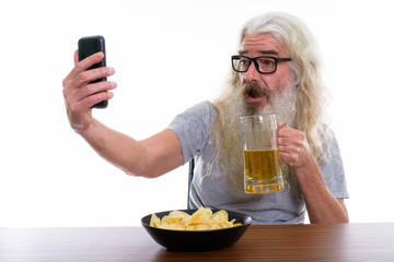 Happy senior bearded man smiling while taking selfie picture wit