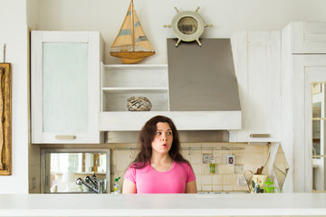 Housewives, emotions and people concept - Surprised young woman in the kitchen at home